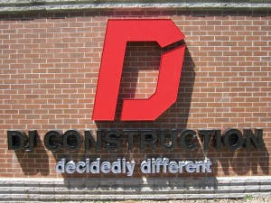 DJ Construction new road sign shows the updated logo, company name, and branding statement.
